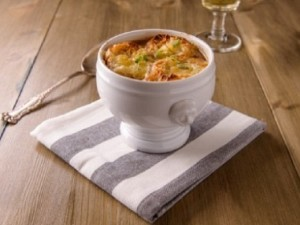 French onion soup on a wood table with a glass of white wine